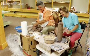 Linda Gholston, left, practices the art of pottery design as instructor, Sheila Hall shares her expertise. (News Photo/Austin Daher)