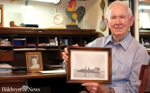 Jimmy Cunningham holds a photograph of the ship he was on while serving in World War II. Cunningham is seated at a desk in his home that was used by his father. (News photo/Jason Collum)