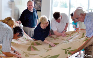Final Stands Board members and Ford family members look over a quilt that was made in 1867 by the women of Bethany Church for the wife of Dr. Samual A. Agnew. The quilt was donated to the Final Stands center. (News Photo/Brenda Daher)